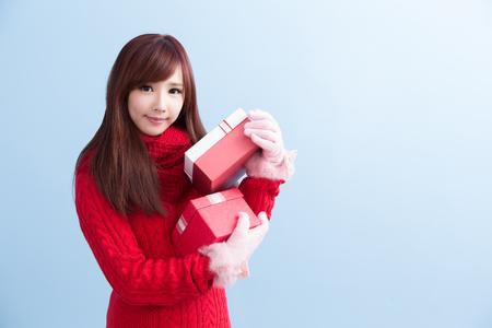 schoonheid woamn nemen geschenk en glimlach aan u in Kerstmis geïsoleerd op blauwe achtergrond, Aziatische