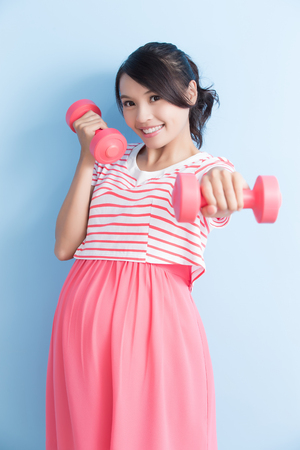pregnant woman hold dumbell and smile isolated on bluebackground, asian
