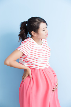 annoyed: pregnant woman have pain isolated on bluebackground, asian Stock Photo