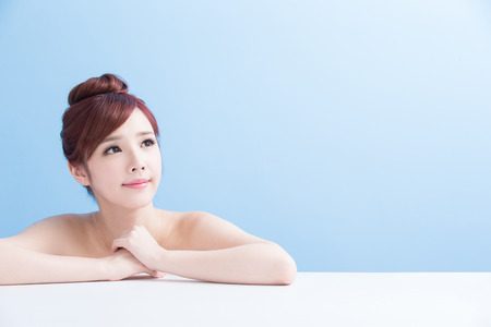 whiten: charming woman face smile and look somewhere close up while lying isolated on blue background, asian girl