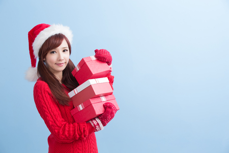 beauty woamn take gift and smile to you in christmas isolated on blue background, asian Stock Photo