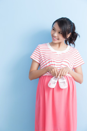 pregnant woman take shoes and look somewhere isolated on bluebackground, asian Stock Photo