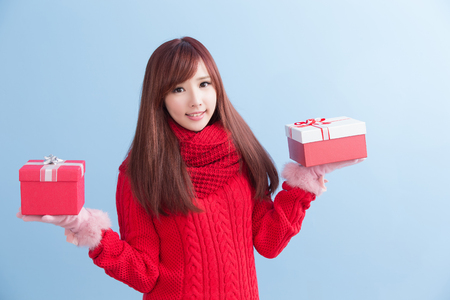 beauty woamn take gift and smile to you in christmas isolated on blue background, asian Reklamní fotografie