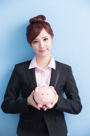business asia: business woman take pink piggy bank and smile to you isolated on blue background, asian