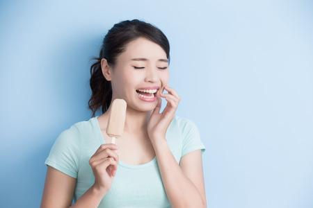 vrouw heeft gevoelige tanden met ijs isolatd op blauwe achtergrond, aziatisch