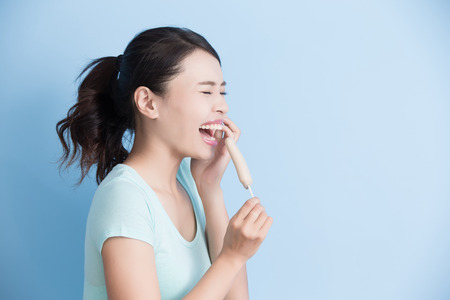 toothache: woman have sensitive teeth with ice isolatd on blue background, asian