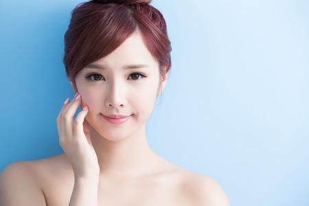 Beauté soins de la peau femme sourire à vous isolé sur bluebackground, asiatique