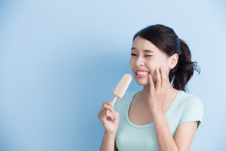 woman have sensitive teeth with ice isolatd on blue background, asian