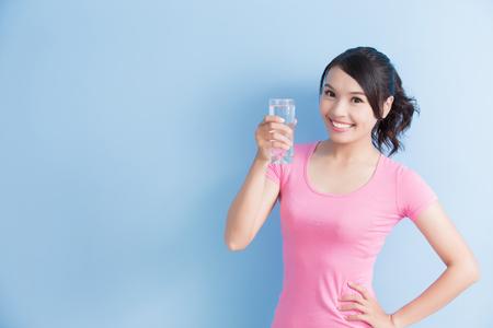 de vrouw drinkt water en glimlacht aan u geïsoleerd op blauwe achtergrond