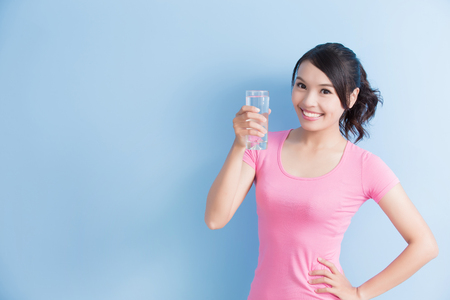 woman drink water and smile to you isolated on blue background Standard-Bild
