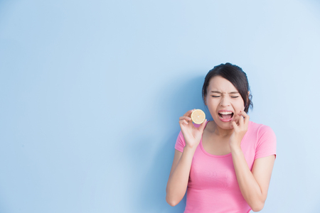 woman eating lemon feel very sour isolated on blue background
