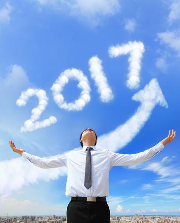 calendario diciembre: feliz año nuevo 2017, el hombre de negocios abrazo 2017 (flecha blanca nube y cielo azul en un día soleado) Foto de archivo