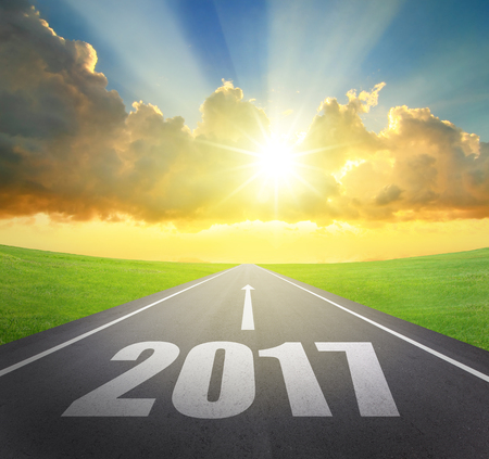 Forward to 2017 new year concept , asphalt road with arrow , date and beautiful sunset and sunshine Stock Photo