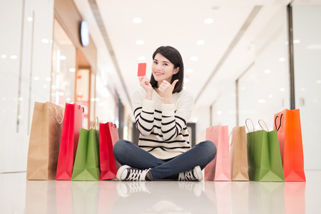 happy shopping young woman show credit card,sit on the floor in the honkong, asian
