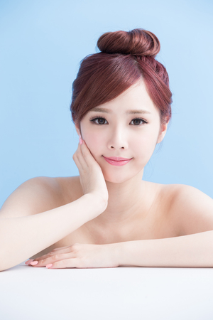 charming girl: charming woman face smile to you close up while lying isolated on blue background, asian girl