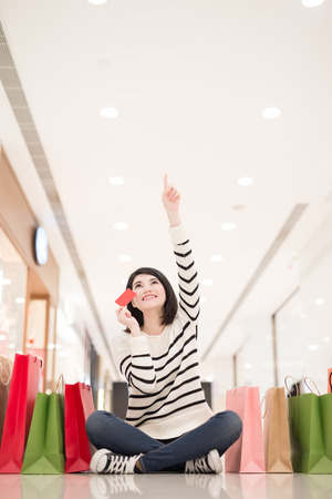 shopping card: happy shopping young woman show credit card,sit on the floor in the honkong, asian