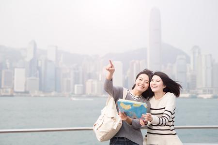 Mujer de dos bellezas tomar el mapa y mostrar algo en Hong Kong