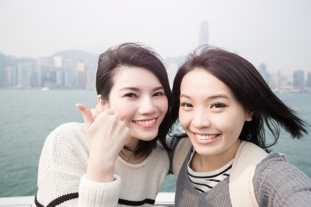 hands free phone: two beauty woman thumb up and selfie in hongkong