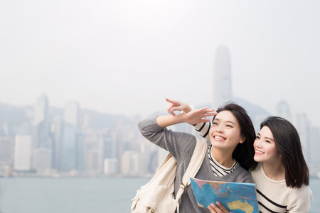 asian group: two beauty woman take map and show something in hongkong Stock Photo