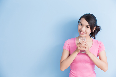 bleach: woman drink water and smile to you isolated on blue background Stock Photo