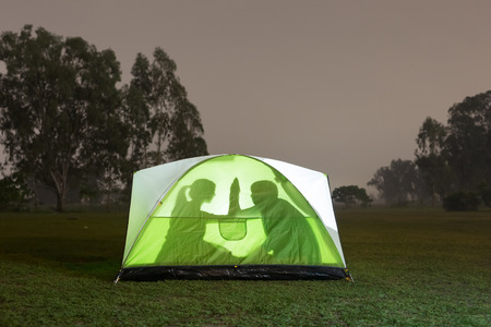 silhouette of couple are camping outdoor with tent, great for your design