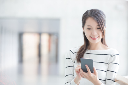 beauty woman use phone and smile happily in hongkong 스톡 콘텐츠