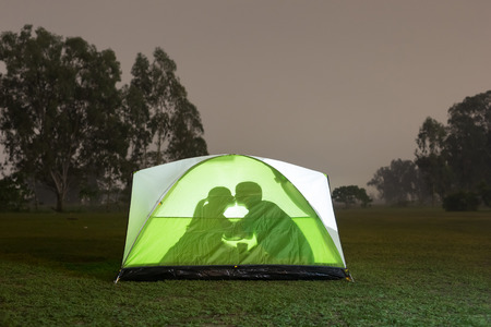 silhouette of couple are camping and kiss outdoor with tent, great for your design Stock Photo