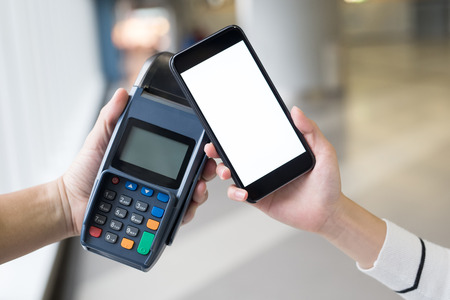contactless: Paying with smartphone. Closeup of man making payment transaction with his mobile phone