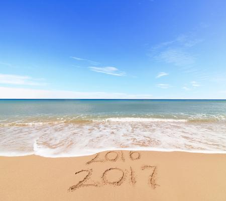 Neues Jahr 2017 ist Konzept kommt - Inschrift 2017 und 2016 an einem Strand Sand, ist die Welle für Ziffern 2016 Standard-Bild - 65442124