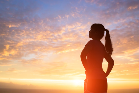 silhouette of sport woman look somewhere with sunlight