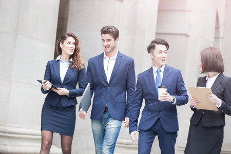 computer office: businesspeople take notebook and coffee walk on the road in hong kong Stock Photo