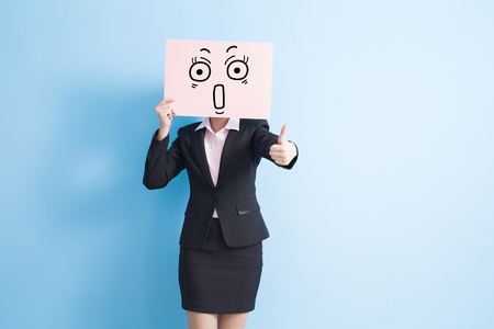 billboard background: business woman take surprise billboard and thumb up, isolated blue background