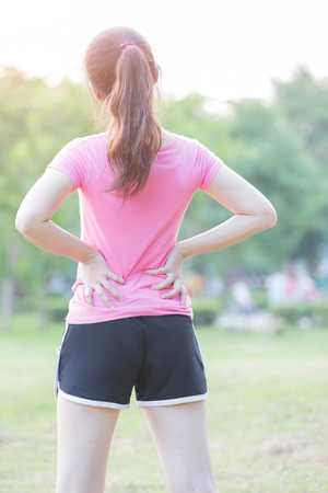 back exercise: sport woman waist injury in the park,great for your design