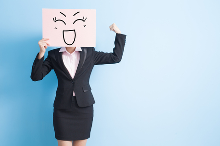 business woman take happy billboard and make a fist, isolated blue background Stockfoto