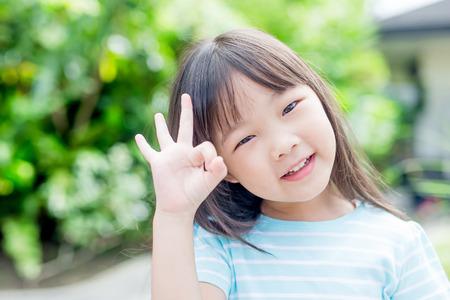 niña sonríe felizmente y te muestra bien en el parque, asiático Foto de archivo
