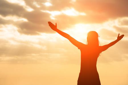 Silueta de la mujer ore con la luz del sol Foto de archivo - 66848343