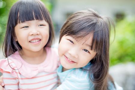 twee kleine meisjes glimlachen gelukkig in het park, Aziatische Stockfoto