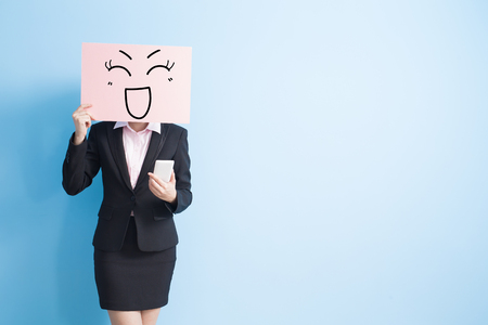 photo: business woman take happy billboard and use smart phone, isolated blue background