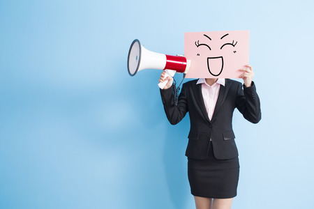 business woman take happy billboard and microphone ,isolated blue background