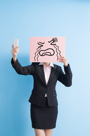 billboard background: business woman take cry billboard and selfie, isolated blue background