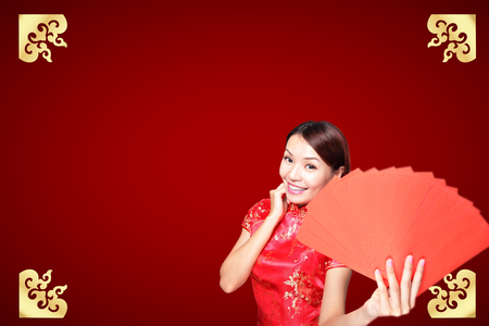 introduce: Smile Chinese woman dress traditional cheongsam and introduce on red background. asian beauty Stock Photo