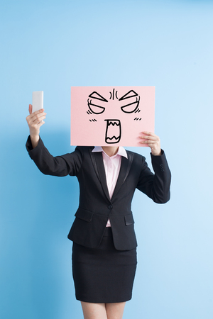lady on phone: business woman take angry billboard and selfie, isolated blue background