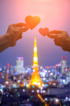 silhouette of romantic lovers hand hold love heart paper in Tokyo Tower with sunset Stock Photo