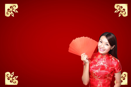 Smile Chinese woman dress traditional cheongsam and introduce on red background. asian beauty Stock Photo