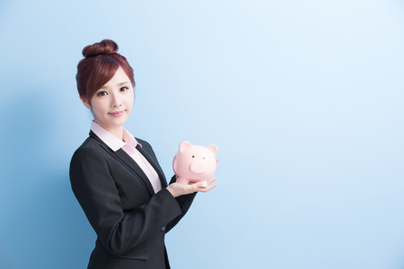business woman take pink piggy bank and smile to you isolated on blue background, asian