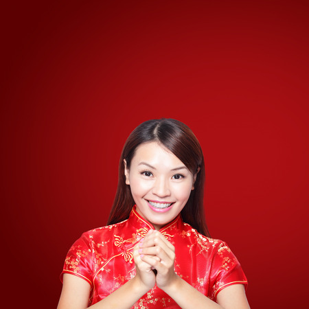 chinese lady: happy Chinese new year. Asian woman with gesture of congratulation isolated on red background Stock Photo