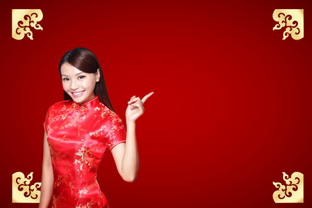 celebrate year: Smile Chinese woman dress traditional cheongsam and introduce on red background. asian beauty Stock Photo