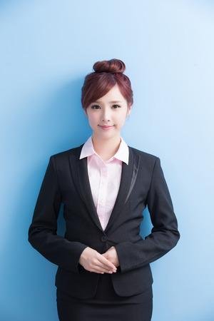 Mujer de negocios sonrisa a usted aislado en fondo azul, asiático Foto de archivo