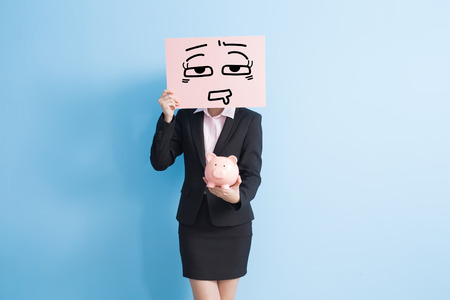 businesswoman take tired billboard and show piggy bank to you isolated with blue background
