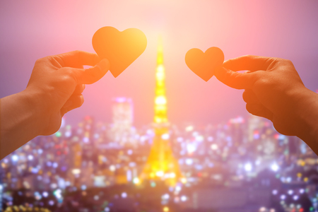 travel woman: silhouette of romantic lovers hand hold love heart paper in Tokyo Tower with sunset Stock Photo